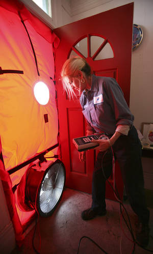 Photo - FILE - In this Feb. 26, 2010 file photo, Roseann Mitchell, of the Community Action Agency, checks airflow readings as part of a blower door test assessment in San Francisco. Electricity prices are expected to rise faster this year than they have since 2009, to a record average of 12.5 cents per kilowatt-hour, according to the Energy Department. And prices are highest in the summer, just when you need more power to run the air conditioner. (AP Photo/Ben Margot, File)