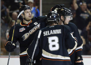 Photo - Anaheim Ducks' Ryan Getzlaf, left, and Teemu Selanne, center, congratulate Corey Perry on his goal against the Florida Panthers during the second period of an NHL hockey game, Sunday, March 23, 2014, in Anaheim, Calif. (AP Photo/Danny Moloshok)