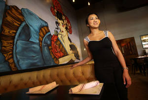 Photo - This May 22, 2014 photo shows Uno Immanivong, owner of Chino Chinatown, posing for a photo in her establishment in Dallas. In a place that prides itself on doing things big, it stands to reason that Dallas' newest hot spot for dining isn't just one restaurant but a new development of nearly a dozen at the foot of a soaring bridge that is the city's newest landmark. (AP Photo/Tony Gutierrez)