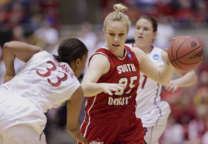 Photo - South Dakota's Nicole Seekamp (35) tries to drive past Stanford's Amber Orrange (33) in the first half of a first-round game in the NCAA women's college basketball tournament in Ames, Iowa, Saturday, March 22, 2014. (AP Photo/Nati Harnik)