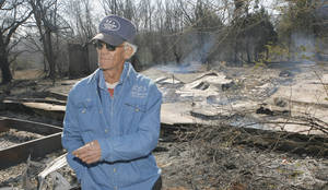 Photo - Bill Sitton looks over the house he grew up in that was destroyed in Thursdays fires north of Lindsay, Friday, April 10, 2009.  Photo By David McDaniel, The Oklahoman