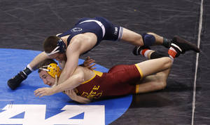 Photo - Penn State's Matt Brown maneuvers above Iowa State's Tanner Weatherman in a 174-pound match in the second round of the NCAA Division I wrestling championships in Oklahoma City, Thursday, March 20, 2014. Brown won the match. (AP Photo/Sue Ogrocki)