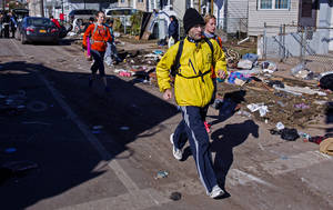 Photo -   Carrying a backpack with goods and supplies, marathon runner Eitan Tabak runs past debris in the hard hit Midland Beach neighborhood of the Staten Island borough of New York, Sunday, Nov. 4, 2012. Background right is marathon runner Michelle Mascioli and far left marathon runner Rachel Wheeler of New York. With the cancellation of the New York Marathon, hundreds of runners, wearing their marathon shirts and backpacks full of supplies, took the ferry to hard-hit Staten Island and ran to neighborhoods hard hit by Superstorm Sandy to help. (AP Photo/Craig Ruttle)