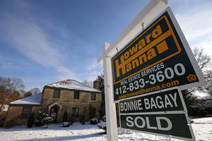 Photo - In this Thursday, Jan. 9, 2014, photo, a sold sale sign hangs in front of a house in Mount Lebanon, Pa. Freddie Mac, the mortgage company, releases weekly mortgage rates on Thursday, Jan. 30, 2014. (AP Photo/Gene J. Puskar)