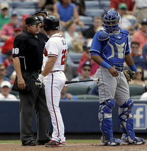 Photo - Atlanta Braves' Dan Uggla, second from left, argues with umpire Doug Eddings, left, after striking out in the seventh inning of a baseball game as Kansas City Royals catcher Salvador Perez, right, looks on, Wednesday, April 17, 2013, in Atlanta. The Royals won 1-0. (AP Photo/David Goldman)