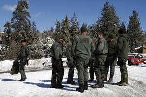 Photo - San Bernardino County Sheriff's deputies gather at the command post in Big Bear Lake, Calif, Saturday, Feb. 9, 2013.  Clear skies allowed aircraft with heat-sensing technology to aid scores of officers searching in the snow-covered San Bernardino Mountains for Christopher Dorner, the former Los Angeles police officer suspected of killing three people in a vengeance-fueled rampage aimed at those he blames for ending his career. (AP Photo/Jae C. Hong)
