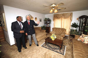 photo - Homeowner Tommy Johnson with auctioneer Louis Dakil in Johnson's living room at 424 NW 91. The home is one of more than 40 properties Dakil will auction on Thursday evening. <strong>PAUL B. SOUTHERLAND - The Oklahoman</strong>