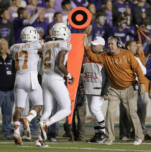 Photo - Texas coach Mack Brown, right, celebrates with cornerback Adrian Phillips (17) and defensive back Mykkele Thompson (2) after Phillips intercepted a pass during the first half of an NCAA college football game against Kansas State, Saturday, Dec. 1, 2012, in Manhattan, Kan. (AP Photo/Charlie Riedel)