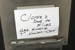 "Photo - ""Closed due to Flooding"" sign on the utility bill payment droop slot in the flooded city office building at 420 West Main, Monday, February 3, 2014. Photo by David McDaniel, The Oklahoman"