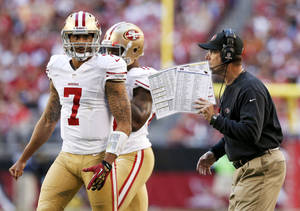 Photo - San Francisco 49ers head coach Jim Harbaugh, right, talks with quarterback Colin Kaepernick (7) prior to a play during the first half of an NFL football game against the Arizona Cardinals, Sunday, Dec. 29, 2013, in Glendale, Ariz. (AP Photo/Ross D. Franklin)