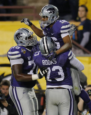 Photo - Kansas State wide receiver Tyler Lockett (16) celebrate his touchdown with teammates Tavon Rooks (73) and Cornelius Lucas (78) during the first half of the Buffalo Wild Wings Bowl NCAA college football game against Michigan, Saturday, Dec. 28, 2013, in Tempe, Ariz. (AP Photo/Matt York)