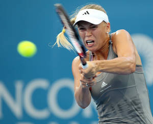 Photo - Caroline Wozniacki, of Denmark, plays a return shot during her first round match against Ksenia Pervak, of Kazakhstan, during the Brisbane International tennis tournament in Brisbane, Australia, Monday, Dec. 31, 2012.  (AP Photo/Tertius Pickard)