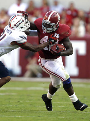 Photo -   Alabama running back Eddie Lacy (42) stiff-arms Florida Atlantic defensive back D'Joun Smith (21) and runs for a first down during the first half of a NCAA college football game on Saturday, Sept. 22, 2012, in Tuscaloosa, Ala. (AP Photo/Butch Dill)