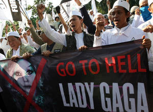 Photo -   Muslim men shout slogans during a rally against U.S. pop singer Lady Gaga's concert that is scheduled to be held on June 3, outside the U.S. Embassy in Jakarta, Indonesia, Friday, May 25, 2012. Lady Gaga might have to cancel her sold-out show in Indonesia because police worry her sexy clothes and dance moves undermine Islamic values and will corrupt the country's youth. (AP Photo/Dita Alangkara)