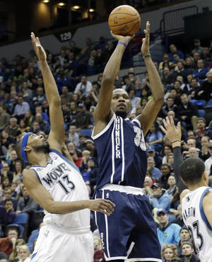 Photo - Oklahoma City Thunder's Kevin Durant shoots as Minnesota Timberwolves' Corey Brewer, left, and Kevin Martin defend during the second half of an NBA basketball game Saturday, Jan. 4, 2014, in Minneapolis. Durant led the Thunder with 48 points in his team's 115-111 win. (AP Photo/Jim Mone)
