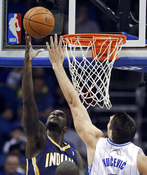 Photo - Indiana Pacers' Lance Stephenson, left, makes a shot over Orlando Magic's Nikola Vucevic, right, of Montenegro, during the first half of an NBA basketball game in Orlando, Fla., Sunday, Feb. 9, 2014. (AP Photo/John Raoux)