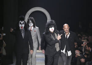 Photo - American fashion designer John Varvatos, right, is accompanied by Rock Band Kiss as he acknowledges the applause of the audience, at the end of his men's Autumn-Winter 2014 collection, part of the Milan Fashion Week, unveiled in Milan, Italy, Saturday, Jan. 11, 2014. (AP Photo/Antonio Calanni)