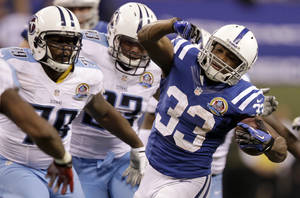 Photo - Indianapolis Colts' Vick Ballard (33) is chased by Tennessee Titans' Jarius Wynn (79) during the second half of an NFL football game, Sunday, Dec. 9, 2012, in Indianapolis. (AP Photo/Michael Conroy)