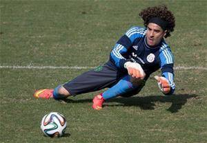 Photo - Mexico goalkeeper Guillermo Ochoa leaps to trap a ball during a training session in Santos, Brazil, Thursday, June 26, 2014.   (AP/Associated Press)