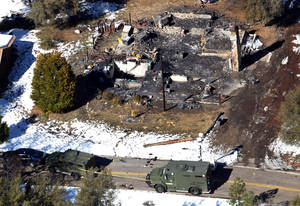 Photo - FILE - This Feb. 13,2013 file photo this aerial photo, law enforcement authorities investigate the burnt-out cabin where accused quadruple-murder suspect Christopher Dorner was believed to have died after barricading himself inside, during a stand-off with police in the Angeles Oaks area of Big Bear, Calif.   A Southern California city's decision not to make good on a promise to pay a $100,000 reward in the case of the rogue ex-Los Angeles officer is the latest wrinkle in the battle over the pot of money that remains unpaid more than six weeks since the fugitive's death.  (AP Photo/The Sun, John Valenzuela,File)