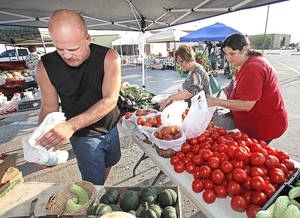 Photo - Randy Peters with Dennis Farm in Blanchard, sells produce to Peggy Lukezic and Karen Delapaz as they shop at the Norman Farmer's Market on Wednesday, August 24, 2011, in Norman, Okla.   Photo by Steve Sisney, The Oklahoman ORG XMIT: KOD