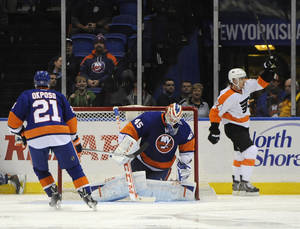 Photo - Philadelphia Flyers' Matt Read (24) celebrates his goal against New York Islanders goalie Anders Nilsson (45) in the second period of an NHL hockey game on Monday, Jan. 20, 2014, in Uniondale, N.Y. (AP Photo/Kathy Kmonicek)