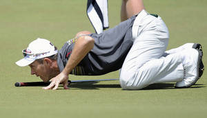Photo - Stuart Manley from Wales lines up a putt on the 18th green during the first round of the World Cup of Golf in Melbourne, Australia, Thursday, Nov. 21, 2013. (AP Photo/Andy Brownbill)