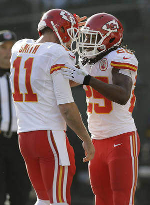 Photo - Kansas City Chiefs running back Jamaal Charles, right, celebrates with quarterback Alex Smith (11) after they connected on a 16-yard touchdown pass against the Oakland Raiders during the second quarter of an NFL football game in Oakland, Calif., Sunday, Dec. 15, 2013. (AP Photo/Marcio Jose Sanchez)