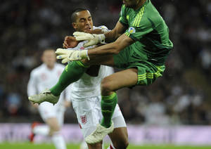 photo -   England's Theo Walcott, left, collides with San Marino's goalkeeper Aldo Junior Simoncini before being taken off the pitch with an injury sustained in the challenge during their World Cup Group H qualifying soccer match at Wembley Stadium in London, Friday Oct. 12, 2012. (AP Photo/Tom Hevezi)