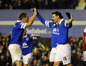Photo - Everton's Gareth Barry right, celebrates with teammate Phil Jagielka left, after he scored the third goal of the game for his side, during their English Premier League soccer match against Fulham at Goodison Park in Liverpool, England, Saturday Dec. 14, 2013. (AP Photo/Clint Hughes)