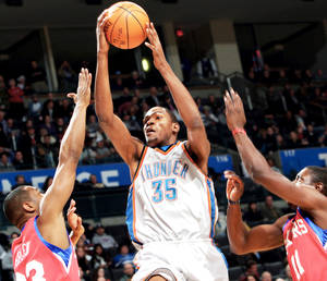 Photo - Oklahoma City's Kevin Durant, center, puts up a shot in front of Philadelphia's Willie Green, left, and Jrue Holiday during Wednesday's game.  Photo By John Clanton, The Oklahoman