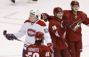 Photo - Phoenix Coyotes' Shane Doan (19) celebrates his goal with teammates Antoine Vermette (50) and Oliver Ekman-Larsson (23), of Sweden, as Montreal Canadiens' Ryan White (53) skates past during the third period of an NHL hockey game on Thursday, March 6, 2014, in Glendale, Ariz.  The Coyotes defeated the Canadiens 5-2. (AP Photo/Ross D. Franklin)