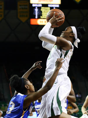 Photo - Baylor guard Odyssey Sims, top, shoots over McNeese State guard Jayln Johnson (3) in the first half of an NCAA college basketball game on Saturday, Dec. 28, 2013, in Waco, Texas. (AP Photo/Waco Tribune Herald, Rod Aydelotte)