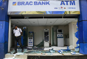 Photo - A security guard walks near ATM machines damaged by Islamic hardliners in Savar near Dhaka, Bangladesh, Monday, May 6, 2013. At least 15 people died in clashes Monday between police and Islamic hardliners demanding that Bangladesh implement an anti-blasphemy law, police said. (AP Photo/Ismail Ferdous)