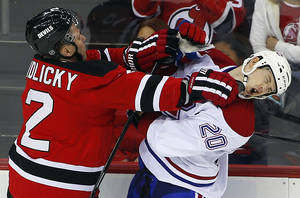 Photo - New Jersey Devils' Marek Zidlicky (2) of the Czech Republic checks Montreal Canadiens' Colby Armstrong (20) during the third period of an NHL hockey game in Newark, N.J., Tuesday, April 23, 2013. The Devils defeated the Canadiens 3-2. (AP Photo/Rich Schultz)