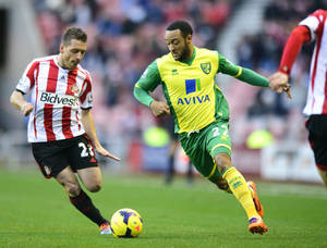 Photo - Sunderland's Emauele Giaccherini, left, and Norwich City's Nathan Redmond vie for the ball during their English Premier League soccer match at The Stadium of Light, Sunderland, Saturday, Dec. 21, 2013. (AP Photo/PA, Steve Drew) UNITED KINGDOM OUT