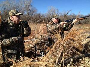 Photo - Duck hunters Roger Stephens (left) and Terry Mock (right) of Oklahoma City try to entice some birds at Fort Cobb Lake on Wednesday. <strong>Photo by Roy Loris</strong>