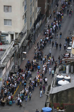 Photo -   Residents line up at a polling station to vote in presidential elections in Caracas, Venezuela, Sunday, Oct. 7, 2012. President Hugo Chavez is running against opposition candidate Henrique Capriles.(AP Photo/Fernando Llano)