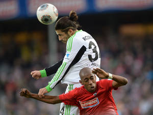 Photo - Wolfsburg's  Ricardo Rodriguez, left, challenges for the ball with Freiburg's  Gelson Fernandes during the German first division Bundesliga soccer match between SC Freiburg and VfL Wolfsburg in Freiburg, southern Germany, Sunday Dec. 8, 2013.  (AP Photo/dpa,Patrick Seeger)