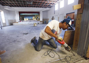 Photo - Harold Harper Jr. chips concrete from the doorway of the cafeteria that is being remodeled at Monroe Elementary. Oklahoma City Public Schools is looking to fill about 20 substitute cafeteria worker positions before school starts Aug. 1. photos BY DAVID McDANIEL, THE OKLAHOMAN