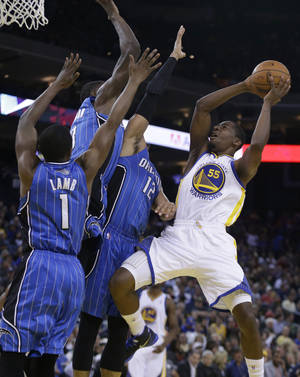 Photo - Golden State Warriors' Jordan Crawford, right, shoots against Orlando Magic guard Doron Lamb (1) and forward Tobias Harris (12) during the second half of an NBA basketball game Tuesday, March 18, 2014, in Oakland, Calif. (AP Photo/Ben Margot)