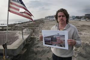 Photo - <p>In this photo taken Nov. 18, 2012, Glenn DiResto poses with a photograph he took after Superstorm Sandy, in the Far Rockaway section of the Queens borough of New York. Diresto took the photo the morning after the storm struck the oceanside community and destroyed the boardwalk, left. (AP Photo/Mark Lennihan)</p>