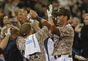 Photo - San Diego Padres Seth Smith is greeted at the dugout after his game tieing home run against the Los Angeles Dodgers in the eighth inning of the opening game of Major League baseball in the United States Sunday, March 30, 2014, in San Diego.  (AP Photo/Lenny Ignelzi)