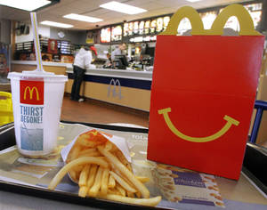 Photo - In this Jan. 20, 2012 photo, the McDonald's logo and a Happy Meal box with french fries and a drink are posed at McDonald's, in Springfield, Ill. McDonald's Corp. reports quarterly earnings on Monday, July 22, 2013. (AP Photo/Seth Perlman)