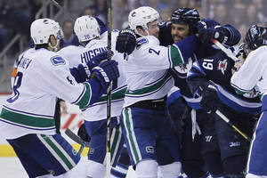 Photo - Vancouver Canucks' Shawn Matthias (27) holds back Winnipeg Jets' Dustin Byfuglien (33) from Canucks' Christopher Tanev (8) during the second period of an NHL hockey game Wednesday, March 12, 2014, in Winnipeg, Manitoba. (AP Photo/The Canadian Press, John Woods)