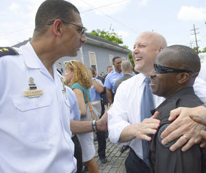 Photo - Darryl J. Albert, New Orleans Police Department Deputy Superintendent, left smiles as New Orleans Mayor Mitch Landrieu congratulates SWAT Team member Frankie Watts Sr. after at a news conference at North Villere and Frenchman Streets in New Orleans, Thursday, May 16, 2013, about two recent arrests made in the Mother's Day parade shooting.  Two brothers with a history of drug arrests and ties to a neighborhood gang each face 20 counts of attempted second-degree murder in a shooting spree that brought a sudden bloody end to the neighborhood Mother's Day parade. (AP Photo/Matthew Hinton)