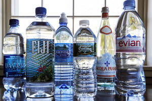 photo - In this Tuesday, March 5, 2013 photo, a selection of bottled waters stands on a kitchen counter in East Derry, N.H. Soda's reign as America's most popular drink could be entering its twilight years, with plain old bottled water making a run for the top spot. Already, bottled water has surged past juice, milk and beer in terms of per capita consumption. The result is that bottled water is slowly closing the gap for the No. 1 spot. (AP Photo/Charles Krupa)