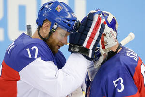 Photo - Czech Republic forward Jiri Novotny comforts goaltender Alexander Salak after their 5-2 loss to the Unites States in the men's quarterfinal hockey game in Shayba Arena at the 2014 Winter Olympics, Wednesday, Feb. 19, 2014, in Sochi, Russia. (AP Photo/David J. Phillip )