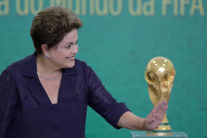 Photo - FILE - In this June 2, 2014, file photo, Brazil's President Dilma Rousseff waves to children at a ceremony where FIFA President Sepp Blatter presented the 2014 World Cup trophy to Rousseff at the Planalto presidential palace, in Brasilia, Brazil. President Rousseff has taken to the nation's airwaves Tuesday June 10, 2104, to deliver a pre-taped address trying to rally the nation behind the World Cup that begins this week. (AP Photo/Eraldo Peres,File)