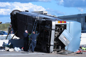 Photo - Indiana State Police investigators inspect the underside of a bus that crashed Saturday, July 27, 2013, on Indianapolis' far north side while carrying teenagers returning from a summer camp in Michigan. Three people were killed and 26 others were taken to local hospitals following the crash, which occurred when the bus exited an interstate ramp and crashed into a concrete retaining wall. Investigators don't yet know what caused the crash about a mile from its destination, Colonial Hills Baptist Church.  (AP Photo/Rick Callahan).